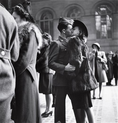 Couple in Penn Station sharing farewell kiss before he